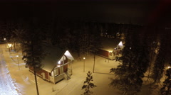 Flying over guest houses in winter holiday village Stock Footage