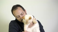A Man Cares A Cat On His Lap - Red Point Siamesse Stock Footage