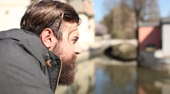 Pensive young man with a beard watching the river Stock Footage