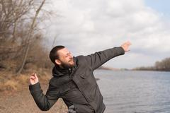 Man dropping a stone into the river Stock Photos