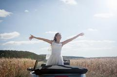 Newlywed bride standing in convertible - stock photo