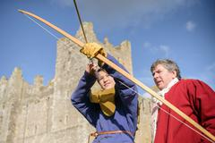 Man teaching history student archery in period dress outside Bolton Castle, a - stock photo