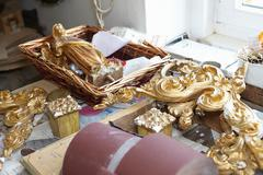 Gold embellishments on work table - stock photo