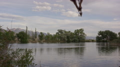 Wide slow motion shot of man swinging into lake / Mona, Utah, United States Stock Footage