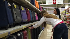 Two womens in a supermarket to buy a suitcase. Select and take one suitcase to - stock footage