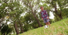 Excited little  boy playing football in park - stock footage