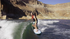 Wide shot of man surfing in churning water / Lake Powell, Utah, United States - stock footage