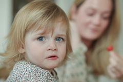Stock Photo of Close up portrait of toddler with mother in background
