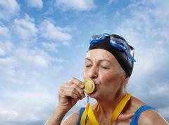 Senior woman wearing swimming cap kissing gold medal - stock photo