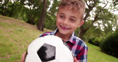 Excited little holding football in hands and is smiling Stock Footage