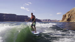 Wide slow motion shot of man surfing in churning water / Lake Powell, Utah, - stock footage