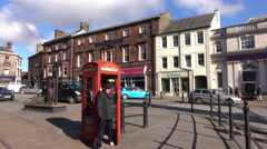 Penrith England woman use red phone booth town center 4K Stock Footage