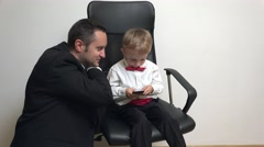 Father and little son with red bow looking together at mobile phone, modern life - stock footage