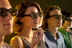 Row of people watching 3D movie, woman with popcorn Stock Photos