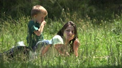 Little child sitting on mother back, enjoying flower fragrance in nature, family - stock footage