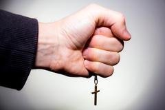 Hand holds a chain with gold crucifix Stock Photos
