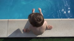 Little kid on the edge of the pool, playing with feet in the water, enjoy summer Stock Footage