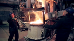 Worker on steel plant operates with liquid metal Stock Footage