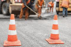 road workers repair the road,  cones in  foreground - stock photo