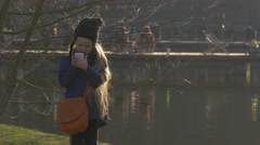 People on a Pier Little Girl Plays Phone River Green Bank of a Lake Walking Stock Footage