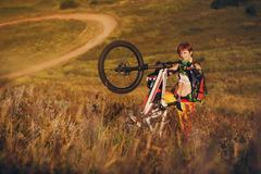 Extreme sports - young woman with downhill bike - stock photo