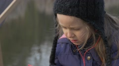 Kid in Hat is Resting on Pier and Listening Music Near to the Water in City Stock Footage