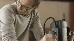 Face carpenter in glasses treats wooden board by plunge router. Manufacturer Stock Footage