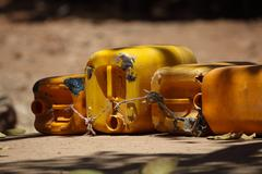 Empty water cans at a well in Africa. - stock photo