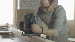 Aged carpenter attentively treat wooden board by plunge router. Manufacturer - stock footage