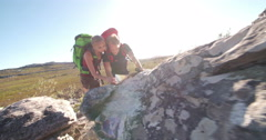Hiking friends orienteering on map and compass during nature adventure Stock Footage