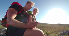 Hiker showing girl friend map on smartphone during outdoor activity Stock Footage