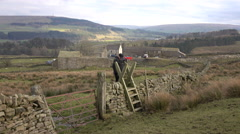 Woman climbing ancient rock fence north England rural 4K Stock Footage