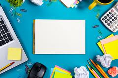 Office table desk with set of colorful supplies, white blank note pad, cup, pen Stock Photos