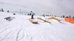 Snowboarder does 180 air onto box in snowboard park - stock footage