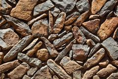 Dry stone wall with blue stones and brown weathered patina. Stock Photos