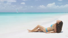 Suntan bikini woman relaxing on beach vacation  sunbathing on travel holidays Stock Footage