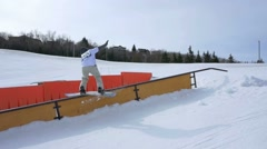 Stock Video Footage of Snowboarder does 180 air onto rail then spins at rail jam contest