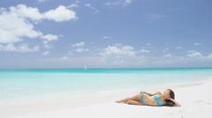 Sexy beach bikini body woman relaxing sun tanning - travel vacation getaway - stock footage