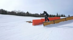 Snowboarder performs front side grind at terrain park Stock Footage