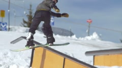 Snowboarder does backside grind on rail in terrain park Stock Footage