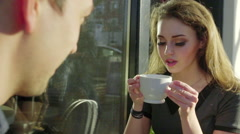 Cute girl blows on her drink to cool it Stock Footage
