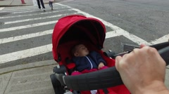 A baby being pushed in a stroller across a crosswalk Stock Footage