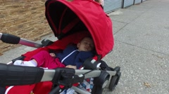A baby being pushed in a stroller down a city sidewalk Stock Footage