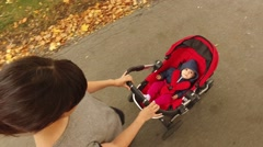 Stock Video Footage of A baby being pushed in a stroller in a city park