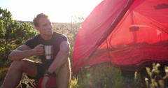 Hiking man drinking coffee next to camping tent in nature Stock Footage