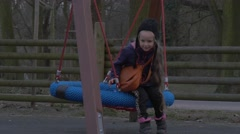 Kid Sits on a Nest Swing Father is Pushing Her Daughter is Playing on a Swing Stock Footage