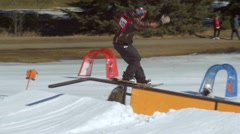 Snowboarder performs tailslide on rail at terrain park Stock Footage