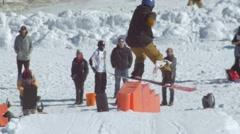 Snowboarder performs frontside boardslide on steps in terrain park Stock Footage