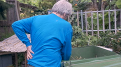 Hand held of an elderly man rubbing his back while working in the yard Stock Footage