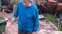 An elderly retired man struggles with a shovel to get a plant out of a pot Stock Footage